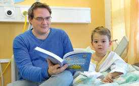 Philippe Oguey et son fils Liam lisent et jouent en attendant l'opération. © Michel Duperrex