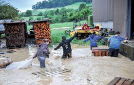 Plusieurs membres de la Jeunesse de Cuarny ont donné un coup de main aux villageois -ici un agriculteur- victimes des intempéries. ©Carole Alkabes