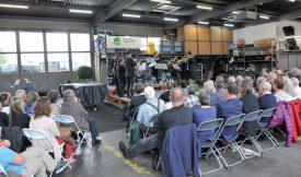 La foule a pris place dans le garage de la voirie yverdonnoise, lieu insolite pour écouter l'Ensemble de cuivres Dixtuor, samedi après-midi. ©Carole Alkabes