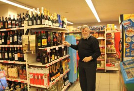 Le gérant du commerce, André Favre, montre le rayon où les bouteilles de spiritueux ont été prises lors du second vol, à l'étalage celui-là. © Roger Juillerat