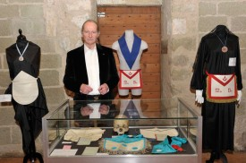 Michel Cugnet au milieu de tenues et objets de rite maçonniques exposés à l'Aula Magna du Château. © Michel Duperrex