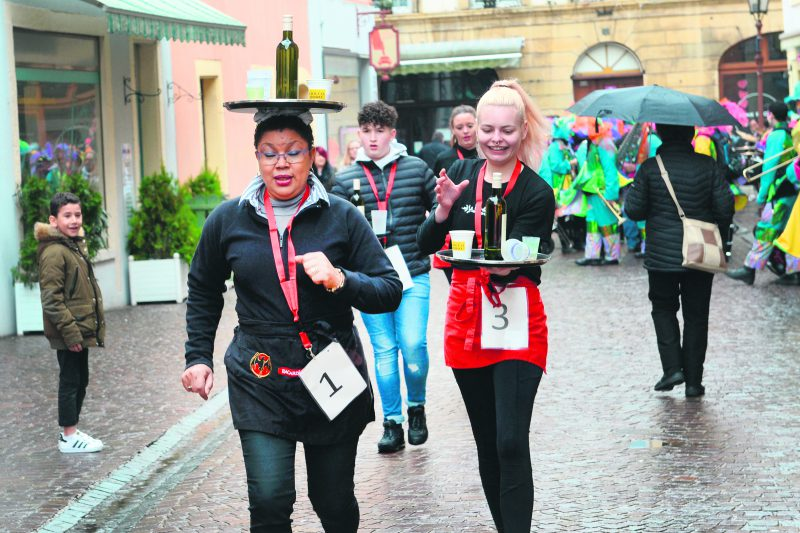 Chacun sa technique pour courir dans les rues du centre-ville avec un plateau. Mais le premier prix de la course des garçons de café a été attribué à Anita (à g.), du Trèfle. © Michel Duperrex