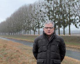 L'inspecteur forestier Pierre Cherbuin avec, en arrière-plan, une partie des peupliers destinés à être abattus dans le cadre du projet de la Thielle. ©Ludovic Pillonel