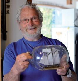 Jean de Bosset tenant l'un des nombreux bateaux en bouteille qu'il fabrique. ©Muriel Aubert