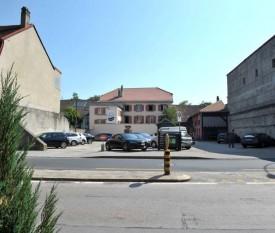 La construction de l'immeuble est prévue sur cette parcelle communale, en face de la Migros, aujourd'hui occupée par un parking. © Duperrex -a