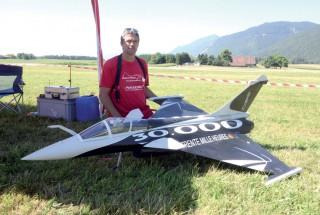 Gilbert Klaus pose aux côtés de sa réplique du Rafale, qui peut atteindre 400 km/h. ©Michel Duvoisin