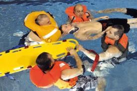 Les gilets de sauvetage compliquent la pose de la minerve... ©Michel Duperrex