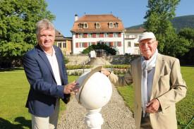 Dominique Willer, directeur de l'EMS Le Château de Corcelles, et l'ancien géomètre Ulrich Petereit, posent avec la réplique du globe gnomonique. ©Michel Duperrex