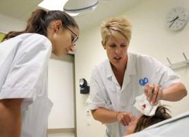 Une infirmière montre une plaie ouverte à la médecin-assistante (à g.) Quelques point de suture seront nécessaires. ©Nadine Jacquet
