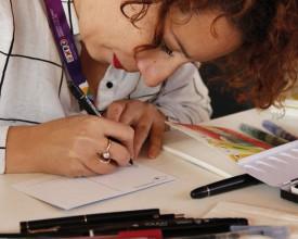 Yasmine Vanderauwera à l'exposition universelle, en train de réaliser un dessin sur carte postale. © Gabriele Merlo, DFAE, Présence suisse