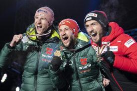 Killian Peier (à dr.) fête sa médaille avec Markus Eisenbichler (au centre) et Karl Geiger. © KEYSTONE/Peter Schneider